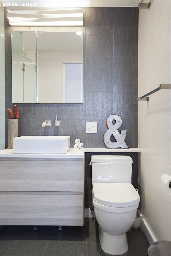 Modern Clinton Hill Co-op bathroom features gorgeous, sleek Ann Sacks gray porcelain tiles, streamlined IKEA vanity with stained oak-effect finish, and slim TOTO toilet.