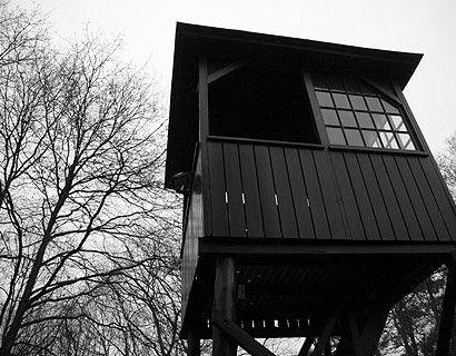 De enige overgebleven orginele wachttoren voor de ingang van voormalig Kamp Amersfoort staat op zijn oorspronkelijke plaats, nu voor het bezoekerscentrum.