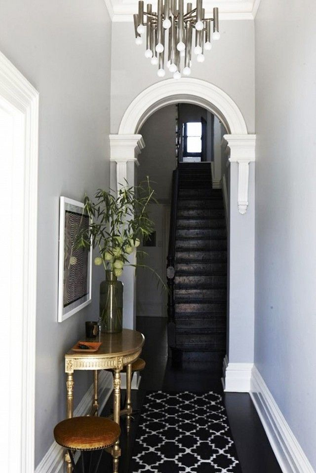 Chic entryway with gray walls, a black staircase, a rug, and a eclectic chandelier MyDomaine
