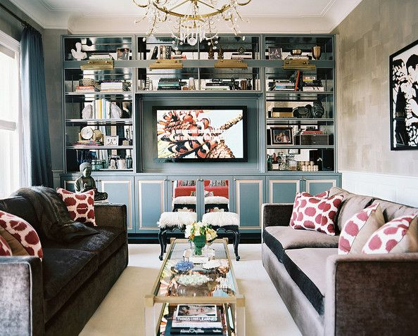 A living space with matching gray couches and blue built-in mirror-backed bookshelves