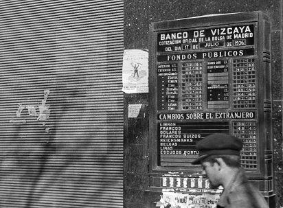 Spain - 1937. - GC - ZONA REPUBLICANA.- MADRID, Marzo de 1937.- Un hombre pasa ante un panel con las cotizaciones de la Bolsa de Madrid correspondientes al día 17 de julio de 1936, situado en la fachada del Banco de Vizcaya