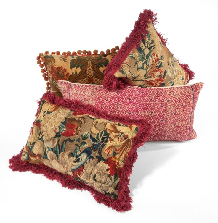 Fragments of antique tapestry and woven silk textiles have been up-cycled as cushions and trimmed with fringe.