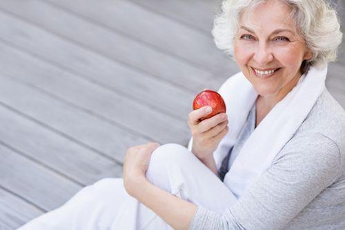 Femme qui mange une pomme pour lutter contre le cholestérol.
