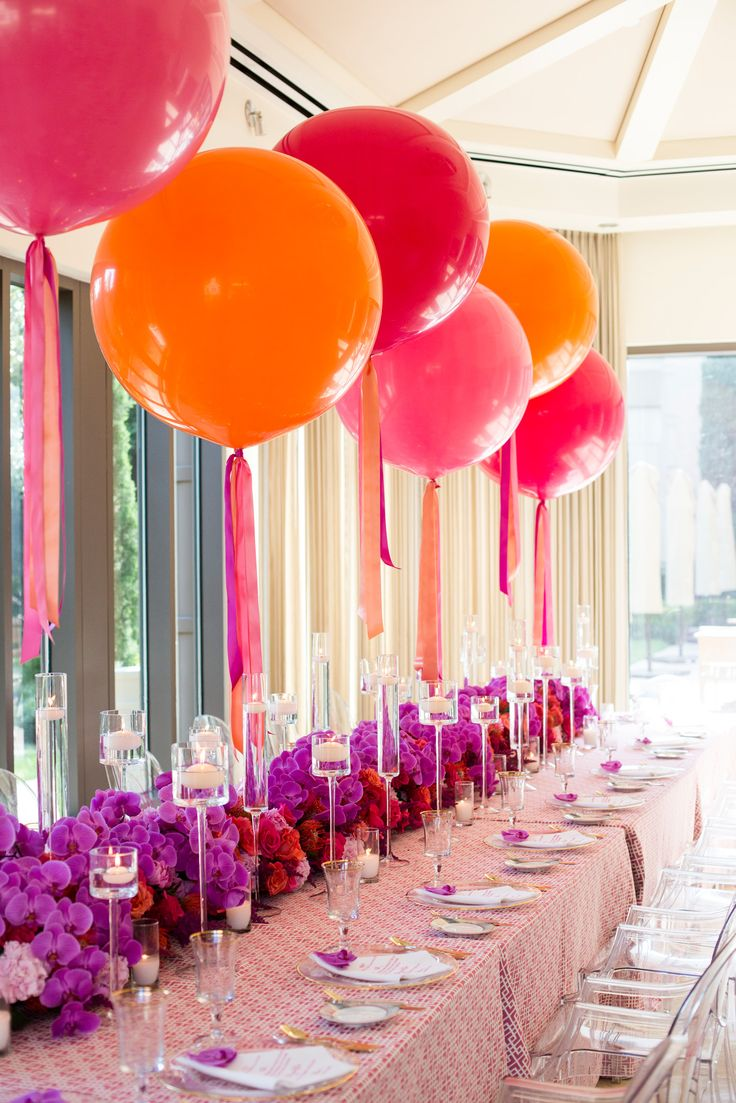 Beautiful head table decoration for your wedding. Orange, red and pink round balloons floating in different heights.