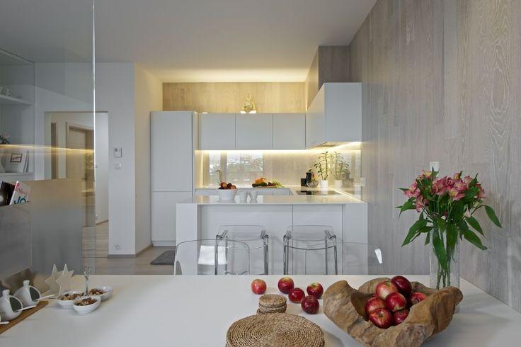 Kuchyňská linka byla vyrobena na míru z bílé lakované MDF. Její součástí je díl, přecházející do barového pultu. Nad částí linky jsou úložné prostory. Stěnu zdobí obklad a zvýrazňuje ji LED podsvícení - ProŽeny.cz