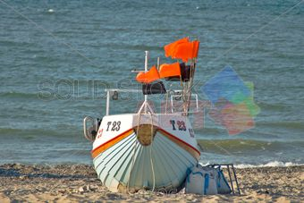 stock photo of green dinghy with orange flag markers on sandy beach outdoors horizontal