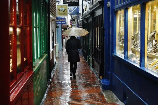 """Una donna passeggia attraverso """"The Lanes"""" zona commerciale a #Brighton, nel sud dell'#Inghilterra"""