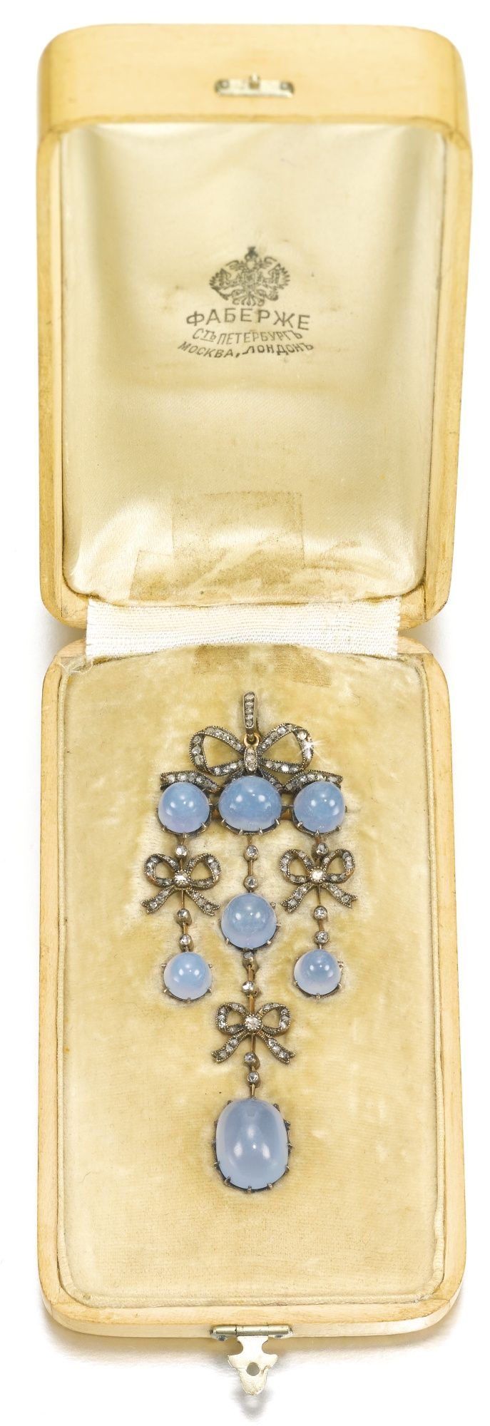 FABERGÉ~ jeweled gold pendant, probably St Petersburg, circa 1910. In neoclassical style, with seven blue chalcedony cabochons suspending from one large and three small rose-cut diamond-set bows, diamond-set suspension loop.