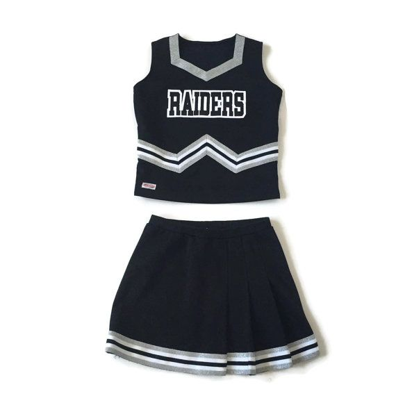 Vintage Raiders cheerleader uniform. Features a crop top and pleated skirt. Black white and metallic silver color scheme. In very good vintage