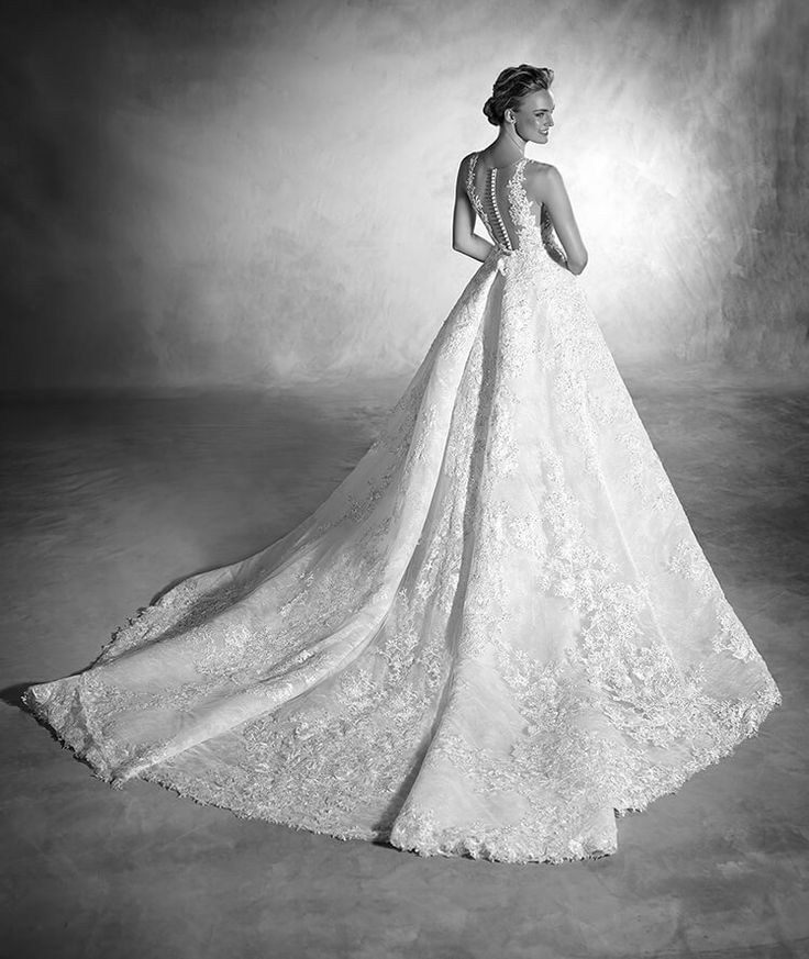 Pronovias Nilay back Who said that minimalism and volume couldn't be one and the same? This mermaid wedding dress with princess overskirt is made of lace and tulle with gemstone and thread embroidery appliqués is proof of it. Additionally, the drop waist and the spectacular V-neckline and the straps meld into a wonderful tattoo-effect back, providing sensuality and femininity. - Download