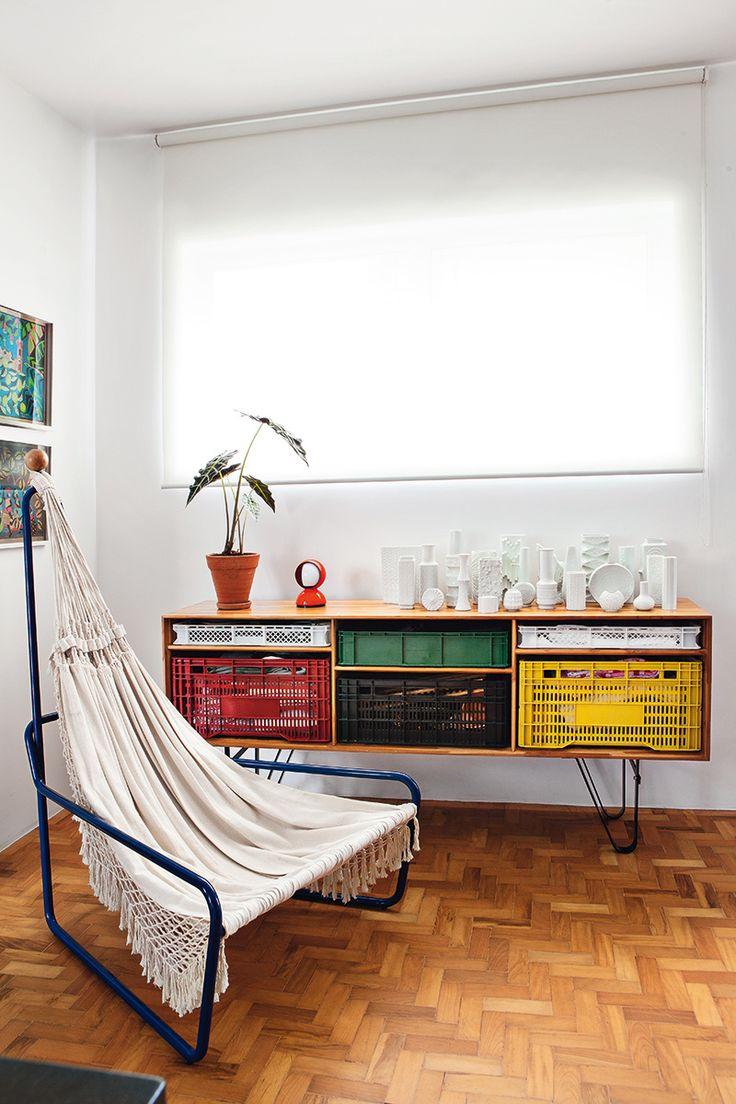 Junto a la cocina, tumbona hecha con una hamaca y aparador customizado con cajas de mercado, ambos creados por Maurício Arruda. Encima, colección de cerámicas alemanas de los 40 y 50.
