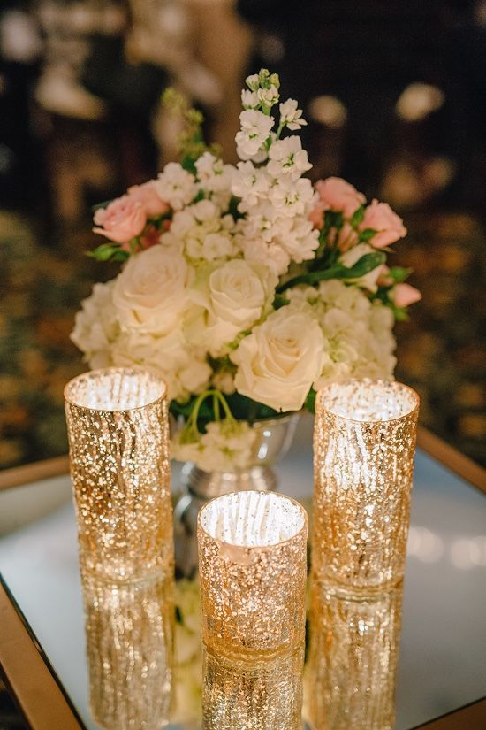Gold Candle Wedding Centerpieces: Want to maximize the glow of your centerpiece candles? Place them on top of a mirror so that the flame's light can bounce off the reflection. You'll get even more gleaming light by using mercury glass votive holders. | 10 Ways to Use Candles at Winter Weddings