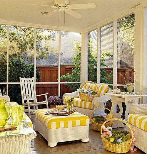 A screened in porch with wicker furniture......