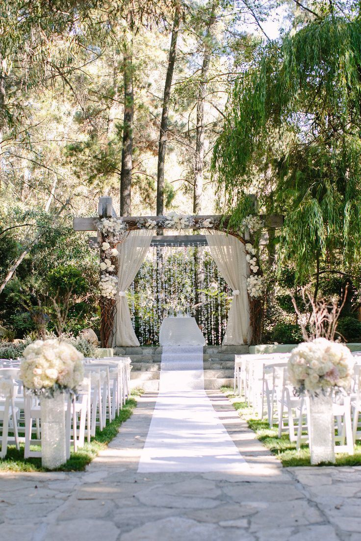 Pergola with hanging flowers and off-white lace draping