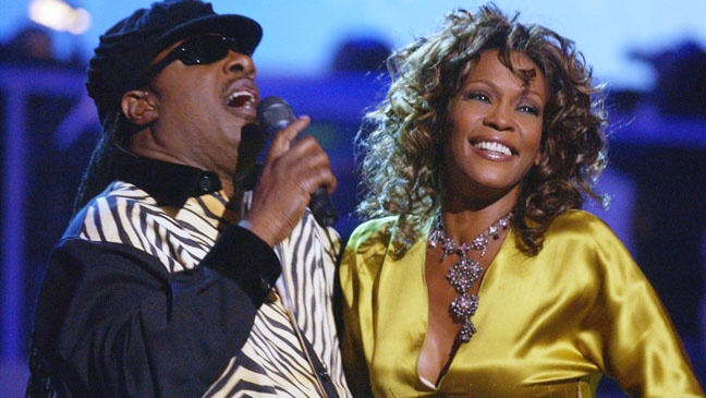 Houston appears radiant performing next to the legendary Stevie Wonder during a 2003 show.