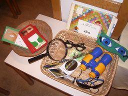 Doos met voorwerpen over zien: bril, verrekijker, lepel, vergrootglas, caleidoscoop, spiegel, afplakpleister, staaf met kleuren