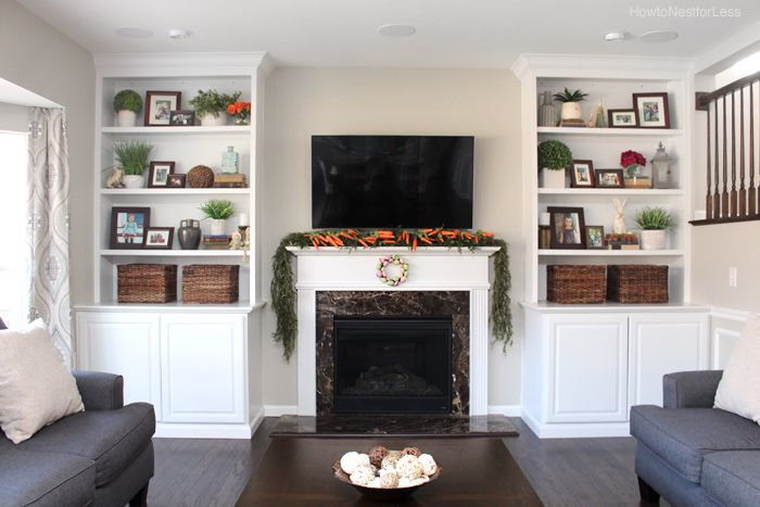 Fireplace with tv above and white built-ins on both sides. Open shelves and cabinets.