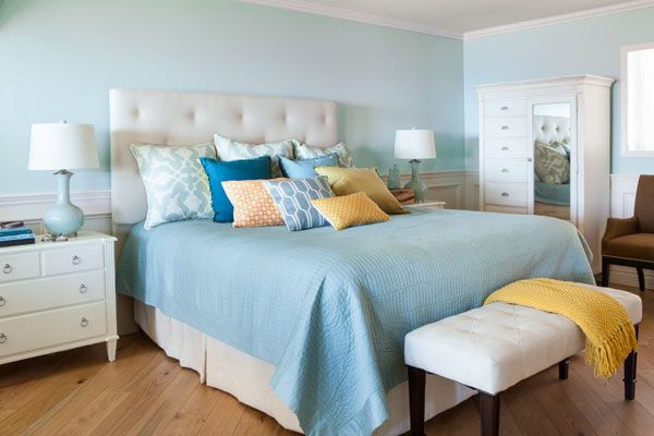 This bedroom's pale blue-green walls, creamy white paneling, neutral furnishings, and natural wood floor add up to a soothing, beach-inspired color palette. | Custom headboard: Tony's Custom Upholstery, San Marcos, CA; 760-591-9686 | Coverlet: @bedbathbeyond | Yellow throw, large yellow patterned pillows, white drum table, and mug: @homegoods | Solid yellow and blue pillows: @crateandbarrel | Jacquard leaf silk pillows and honeycomb crewel pillows: @westelm | Bench: @pier1imports