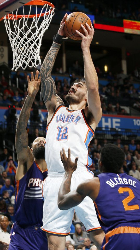 Oklahoma City's Steven Adams (12) takes the ball to the hoop between Phoenix's Tyson Chandler (4), left, and Eric Bledsoe (2) during an NBA basketball game between the Oklahoma City Thunder and the Phoenix Suns at Chesapeake Energy Arena in Norman, Okla., Saturday, Dec. 17, 2016. Oklahoma City won 114-101. Photo by Nate Billings, The Oklahoman