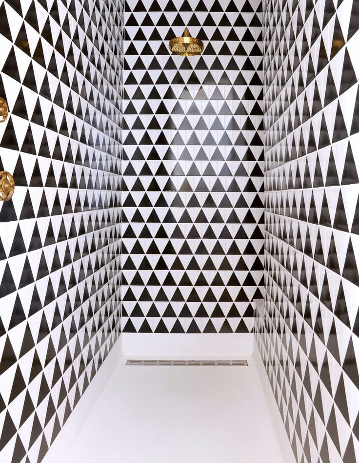 Shower in a Manhattan Penthouse by Nate Berkus, with a sleek triangular pattern in black and white.