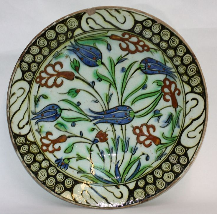 Iznik plate, 17th century, decorated with tulips a Ref: TL177  Iznik plate, 17th century, decorated with tulips and stylised anemones, with a black swirling cloud border, diameter: 10 1/2in. 26.5cm.