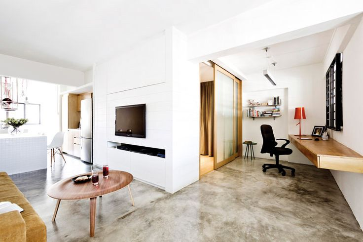 "HDB in Singapore ""The uneven-toned cement screed floor gives and edgy feel to the minimalist space. Coffee table, side table, red lamp and clear glass vase from Xtra."""