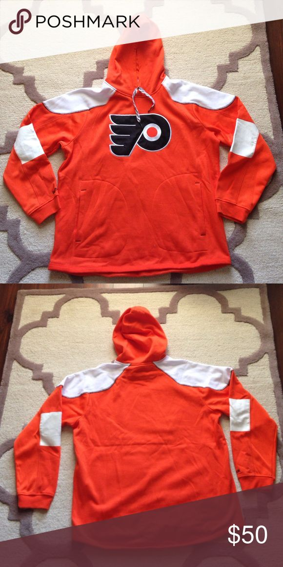 """Flyers Jersey Style Hoodie - NHL Shop Orange Flyers hoodie with white shoulder and elbow details. Resembles the style of NHL jerseys. Official Flyers merchandise. Part of the Reebok Face Off Collection. Materials - 60% Cotton, 40% Polyester. Measurements - Waist: 44"""", Sleeve: 31.5"""", Length: 29"""" Reebok Sweaters"""