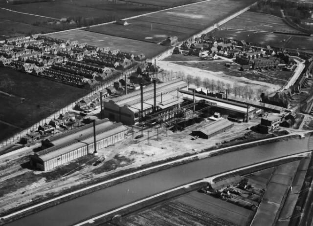 Luchtfoto van het kantoor en fabriek van de N.V. Nederlandse Staalfabrieken DEMKA voorheen J.M. de Muinck Keizer (Havenweg 7) te Zuilen, gelegen tussen Merwedekanaal (onder), Amsterdamsestraatweg (links) en Havenweg (rechts), uit het noordwesten met links boven, tussen Amsterdamsestraatweg en Daalseweg, de wijk Elinkwijk; aan de andere zijde van de Amsterdamsestraatweg de in aanbouw zijnde wijk rondom de Stephensonstraat met daarachter het Park van Kol, het latere Julianapark.1923