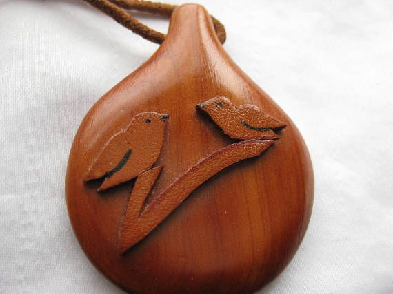 nice two birds on a branch pendant , different suede on wood detail, strung on a suede cord.