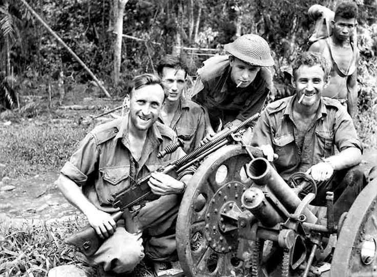 Australian soldiers and a Papuan guide show off a captured Type 92 Battalion Gun and a Type 1 Juki heavy machine gun following the Battle of Oivi-Gorari. Papua New Guinea 23 Nov 1942.