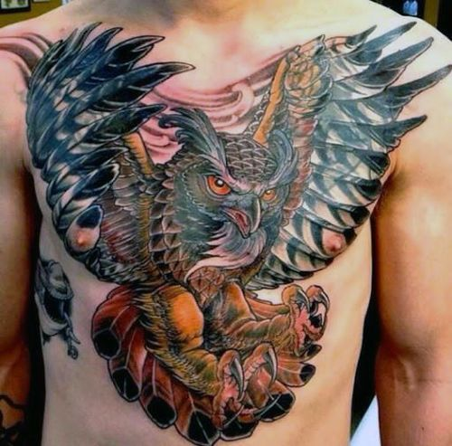 Flying owl tattoo on the chest