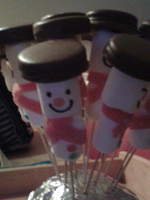 Sneeuwpop traktatie.  Prik twee witte marshmallows op een sateprikker. Gebruik een zuur matje voor de sjaal en zet vast met suikerglazuur. Gezichtje tekenen met cupcake chocolade stift. Neus en knoopjes van confetti cupcake decoratie, vastgemaakt met suikerglazuur. Pet is gemaakt van dubbel oreo koekje, geprikt op satéstokje en extra vastgemaakt met suikerglazuur.