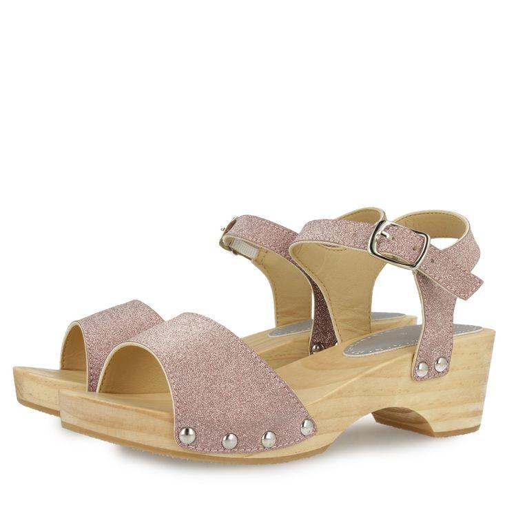 Sandalias de glitter plateado con detalle de tachas plateadas y suela de madera. Cierre al tobillo con hebilla. Tacón de 4,5cm. Corte y forro sintéticos, plantilla de material vegetal.