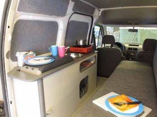 La cocina y sofá / cama en una conversión de mini autocaravana.