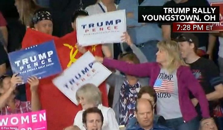 Prior to being removed by security, the protester waved a Soviet Union flag. Trump supporters tried to block it from the camera with their signs