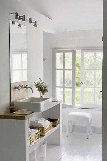 reforma baño con lavabo sobre mueble de obra y grifos empotrados, suelo de parquet pintado de blanco.
