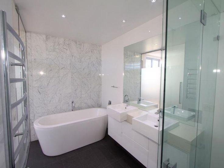 Black floor tiles, white/grey marble feature wall tiles, white vanity