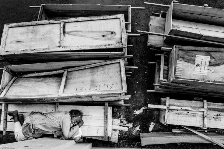 2014, Spot News, 3rd prize stories, Rahul Talukder, Bangladesh COLLAPSE OF RANA PLAZA An old man sleeps on coffins at a makeshift morgue in a schoolyard near Rana Plaza.