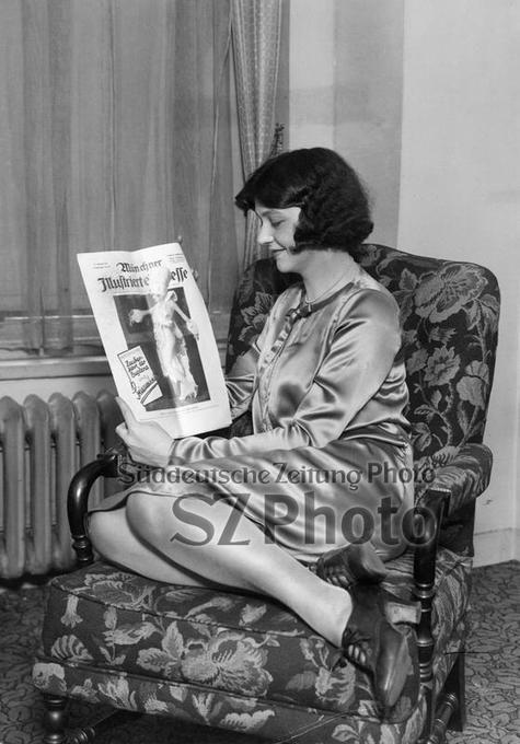 Eine junge Frau präsentiert eine Ausgabe der Zeitschrift 'Münchner Illustrierte Presse' aus dem Dezember 1925.