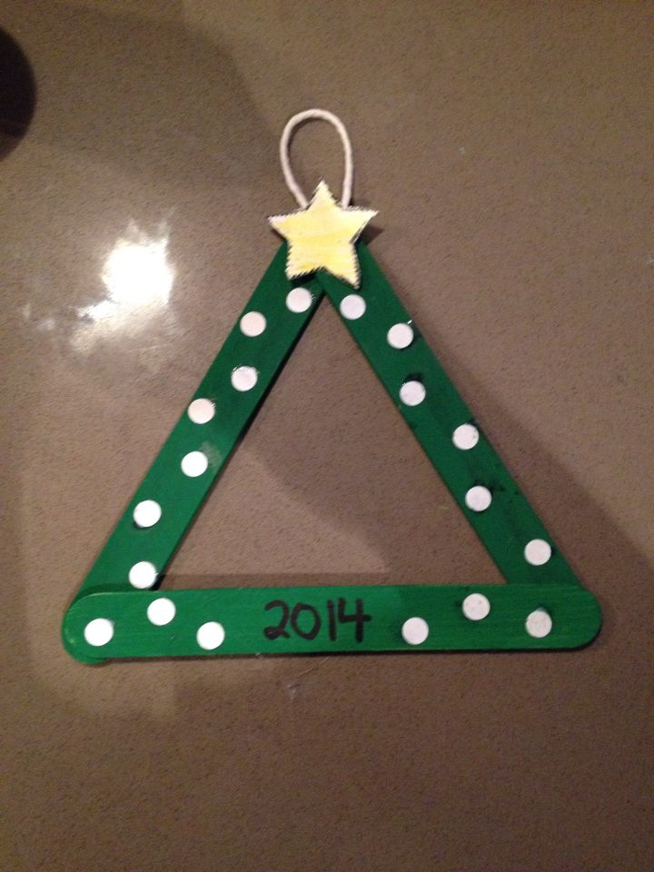 Parent Christmas gift from students. Easy to make! Painted Popsicle sticks. Hot glue gunned into a triangle. Then hot glue gunned the string and star on top. Used permanent marker for the year. And used hole punch cut outs for the snow. All we have to add is the picture for this adorable ornament!