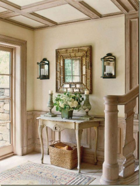 The vase of blossoms add just the right height and scale, preventing the mirror from overpowering the table and objects below.