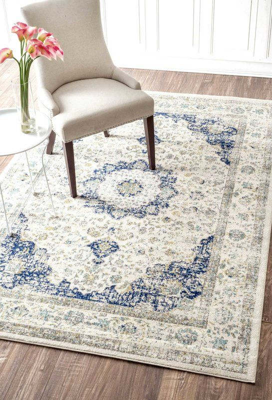 Bring antiqued inspiration and a patterned foundation to any room with this area rug. Machine woven in Turkey from 100 percent polypropylene, this synthetic rug's .25-inch pile is embellished with a faded Persian-inspired, floral motif in a white and blue color palette. Use this sophisticated area rug as a warm anchor to a contemporary aesthetic in your living room. Paint paneled walls white with matching trim to contrast wood floors. Roll out this rug, and then top it with a sleek glass…