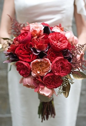 The bride will carry a textured clutch bouquet of dark red peonies, red sweet peas, red garden roses, antique pink garden roses, ivory garden roses, peach garden roses, silver brunia, gray dusty miller, gold seeded eucalyptus, and burgundy astilbe wrapped in soft gold ribbon with the stems showing