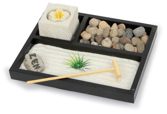 Zen-Garten, Steindekor. Mehr als eine schöne Dekoration auf bspw. Schreibtischen ist dieser Artikel aus schwarz lackiertem Holz. Der Sand wird im Rahmen mit der kleinen Harke formvollendet geglättet und die innere Ruhe stellt sich ein. Nun die kleinen Kiesel, den gemusterten Teelichthalter und das Grasbüschel aus Kunststoff platziert – schon bewirkt das Arrangement beim Betrachter ein Gleichgewicht der Empfindungen. Inkl. Teelicht in Form einer zarten Blüte.