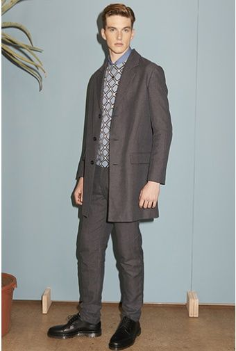 A.P.C. | LOOK 1 - Long jacket in grey blue / gray blue end-on-end cotton-linen blend. R�my jumper / sweater in blue extra-fine Merino wool with large two-tone check print. Gary overshirt in thin blue stonewashed denim. Classic trousers / pants in grey / gray herringbone cotton-wool blend. Brian necklace in golden brass and black resin. Derbies in smooth black leather with notched sole.