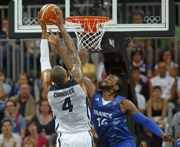 Tyson Chandler (L) of the U.S. is defended by France's Ronny Turiaf during their men's Group A basketball match at the London 2012 Olympic Games in the Basketball arena  July 29, 2012.