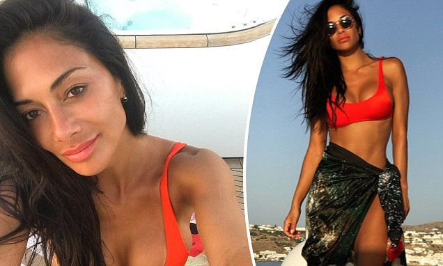 Posing in front of the idyllic coastline, Nicole, 39, shows off her lithe physique in a vibrant red bikini top and patterned sarong.