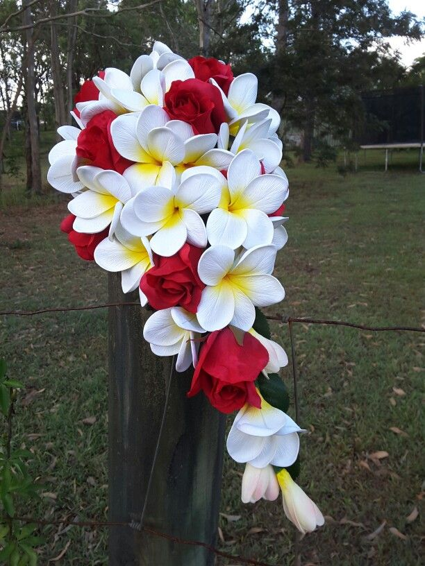 Frangipani and red roses in a teardrop bouquet