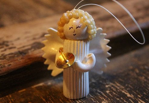 This is a very cute Angel made by me using different types of pasta. She is painted white and has a hand drawn face. She is holding a thumbtack