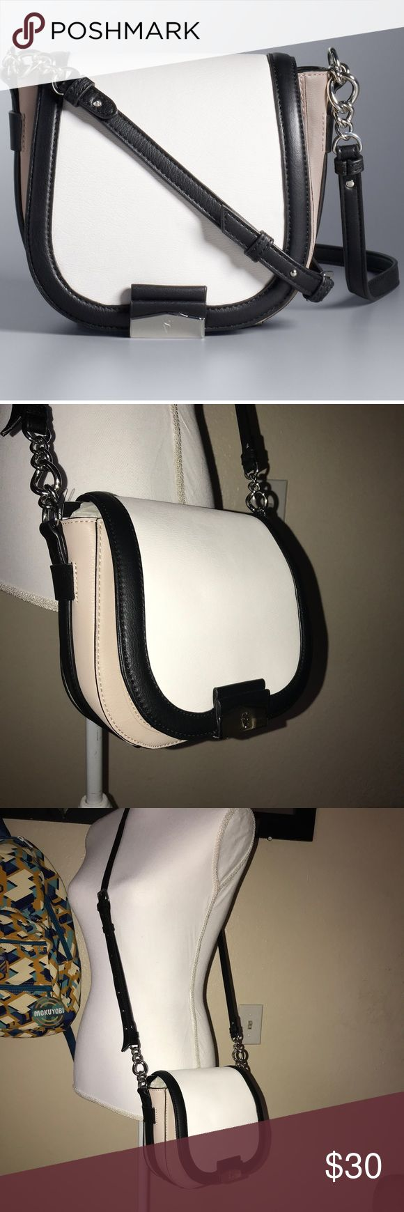 "Simply Vera Wang cross-body Bag Black Tan White Simply Vera Vera Wang Monte Saddle Bag purse with chain link strap accent and silver tone hardware. Adjustable shoulder strap with 23"" drop length. Magnetic clasp closure faux leather.  7""H x 8""W x 4""D Simply Vera Vera Wang Bags Crossbody Bags"